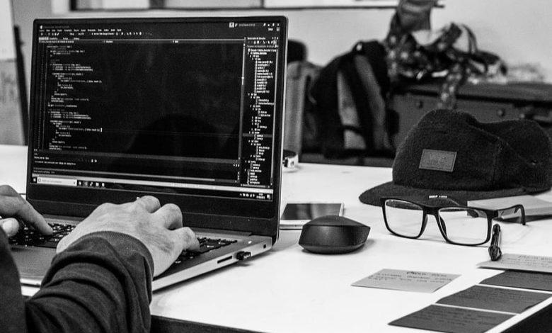grayscale photo of man using laptop coding 780x470 1